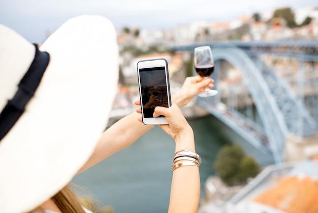 Touriste de jeune femme photographiant un verre de vin de porto se reposant sur la terrasse avec la vue superbe de paysage urbain sur la ville de porto au portugal