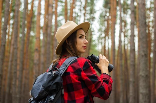 Touriste de jeune femme avec sac à dos, chapeau et chemise à carreaux rouge tenant des jumelles dans la forêt.