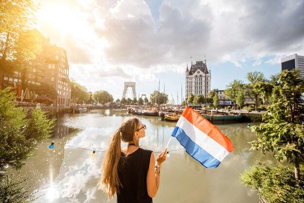 Touriste de jeune femme se tenant en arrière avec le drapeau néerlandais au vieux port dans la ville de rotterdam