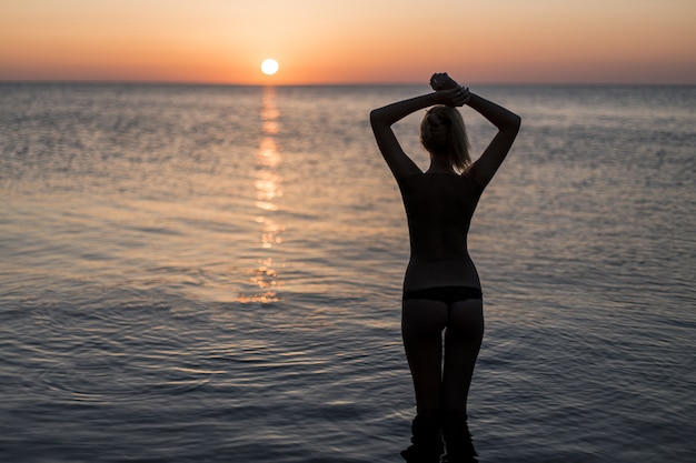 Touriste en maillot de bain en regardant le lever du soleil