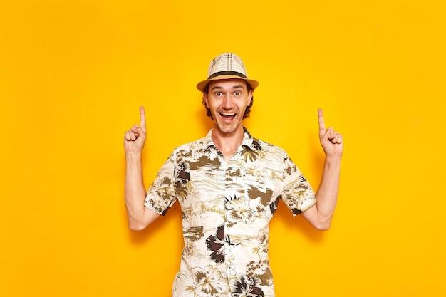 Un touriste masculin heureux au repos pointe ses doigts au-dessus de lui dans un espace vide pour le texte