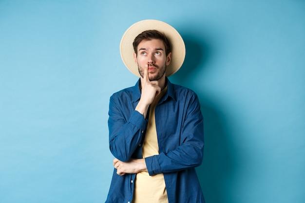 Touriste masculin réfléchi pensant aux vacances d'été, regardant de côté avec un visage pensif, touchant la lèvre et réfléchissant au prochain voyage, debout sur fond bleu.