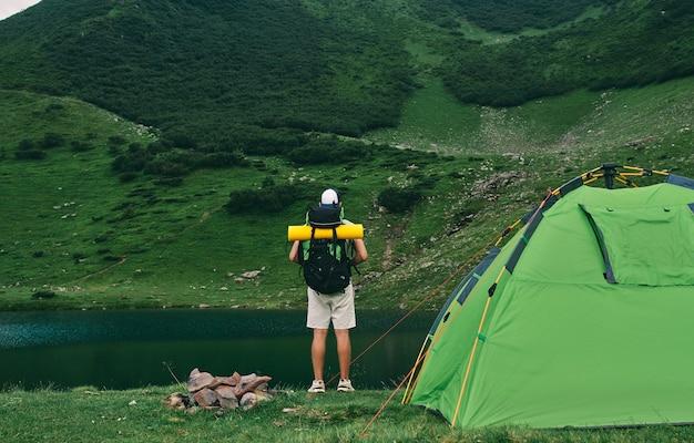 Un touriste masculin avec un sac à dos et un tapis en caoutchouc se tient près d'une tente au bord du lac. un jeune randonneur au pied des montagnes verdoyantes. voyage, vacances, tourisme.