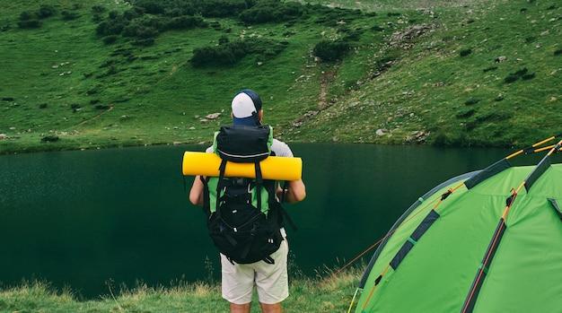 Un touriste masculin avec un sac à dos et un tapis en caoutchouc se tient près d'une tente au bord du lac. voyage, vacances, tourisme.