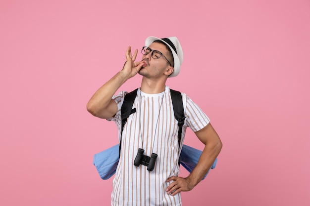Touriste masculin de vue de face marchant avec le sac à dos sur le touriste rose d'émotion de couleur de mur