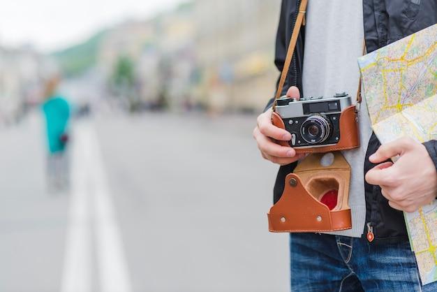 Touriste méconnaissable avec caméra et carte