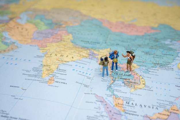Le touriste miniature lgbtq se tient et marche sur la carte de la thaïlande sur la carte du monde.