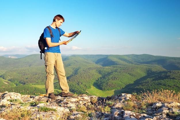 Un touriste en montagne a lu la carte. homme au sommet de la montagne. notion de tourisme