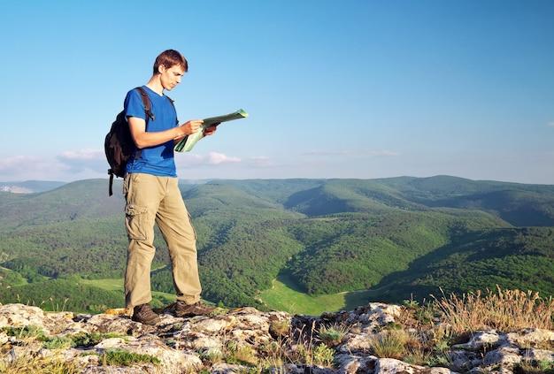 Un touriste en montagne a lu la carte.