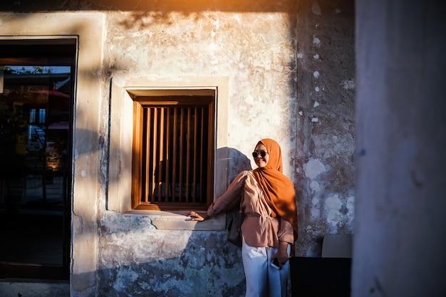 Touriste musulmane debout sur un escalier dans une atmosphère de maison chinoise, femme asiatique en vacances. concept de voyage. thème chinois.