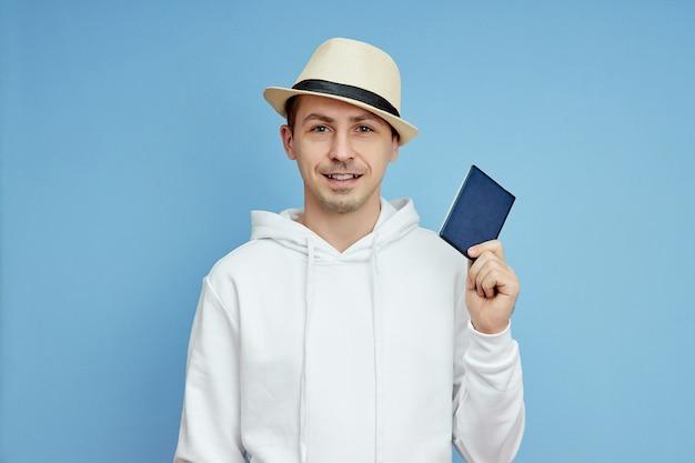 Touriste de portrait d'homme avec un passeport à disposition, homme au chapeau