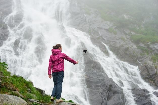 Touriste prenant un selfie posant près d'une superbe cascade rocheuse dans les montagnes