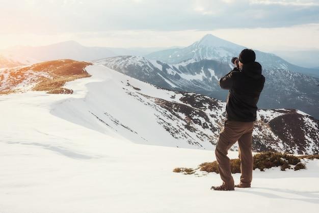 Le touriste regarde le paysage. photographe au sommet de la montagne