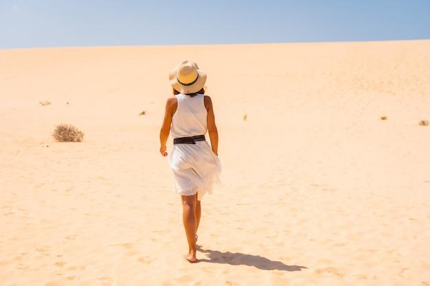 Touriste en robe blanche et chapeau marchant à travers les dunes du parc naturel de corralejo, fuerteventura, îles canaries. espagne