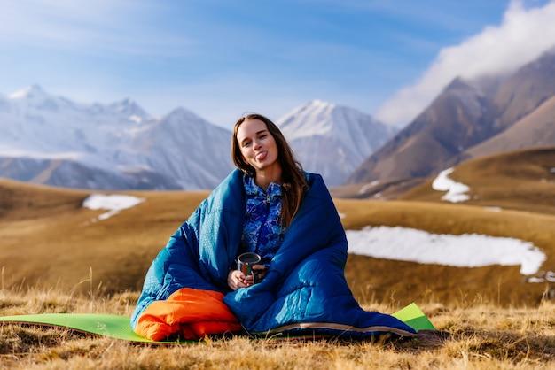 Une touriste s'assoit et montre sa langue dans le contexte des hautes montagnes