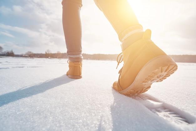 Touriste s'éloignant dans la neige au coucher du soleil