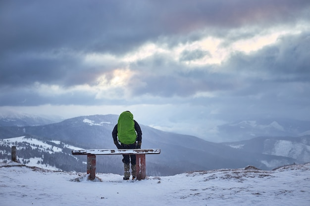 Touriste avec sac à dos et panorama de montagnes. paysage d'hiver. randonnée