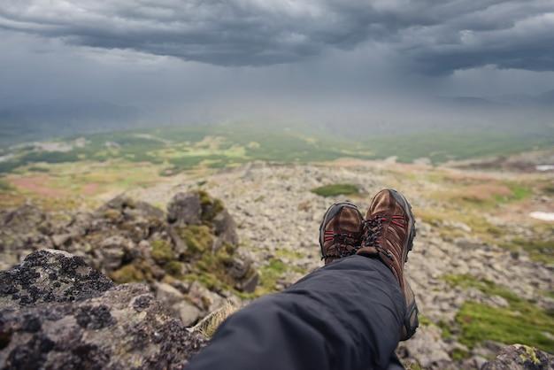 Un touriste se repose au sommet des montagnes avant la pluie vue d'en haut avec un ciel d'orage
