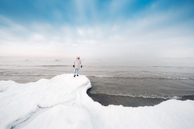 Un touriste se tient sur la rive de la mer baltique en hiver. hiver près des états baltes de tallinn.traveler près de la mer en hiver