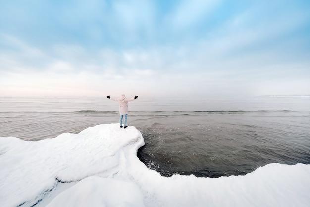 Un touriste se tient sur la rive de la mer baltique en hiver.