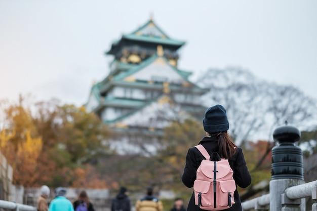 Touriste solo voyageant au château d'osaka en automne, visite d'un voyageur asiatique dans la ville d'osaka, au japon. concept de vacances, de destination et de voyage