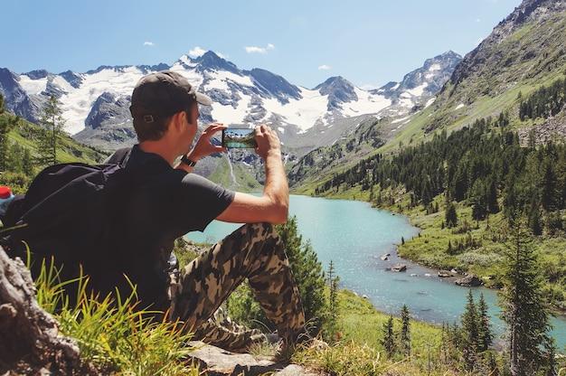 Un touriste en t-shirt noir prend des photos avec un téléphone intelligent au sommet du rocher. paysage vallonné de rêve ci-dessous. le magnifique paysage des montagnes de l'altaï. lac multinskoe
