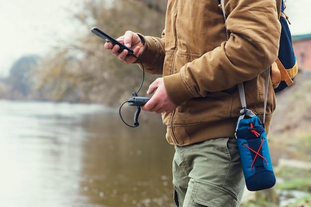Le touriste tient un chargeur portable avec un smartphone à la main. un homme sur le fond d'un lac avec un sac à dos charge le téléphone avec power bank. concept sur le thème du tourisme.