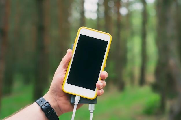 Le touriste tient un chargeur portable avec un smartphone à la main. homme sur fond de nature avec des verts.