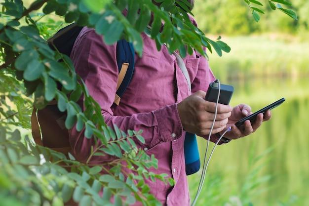 Le touriste tient un smartphone avec un chargeur portable dans ses mains. l'homme avec une banque d'alimentation charge le téléphone dans le contexte de la nature et de la forêt.