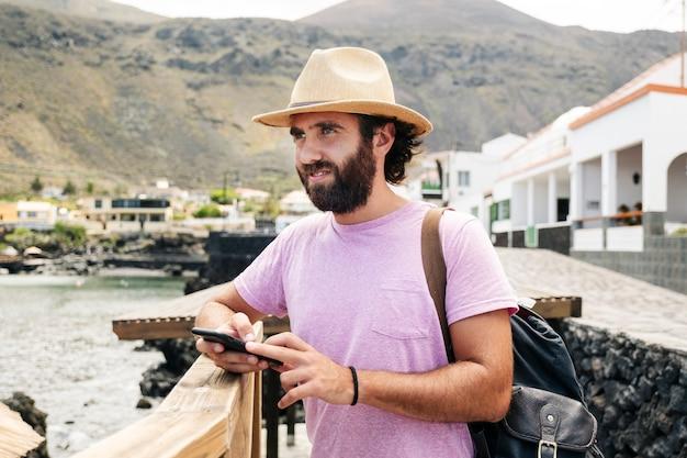 Un touriste utilise un téléphone mobile dans une ville côtière d'el hierro, îles canaries