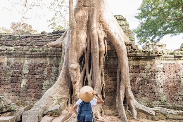 Un touriste visitant les ruines d'angkor au milieu de la jungle, complexe de temples d'angkor wat, destination de voyage au cambodge. femme, chapeau traditionnel, vue postérieure