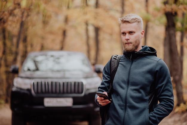 Le touriste voyage en voiture. l'homme au téléphone regarde où il se trouve sur le navigateur.