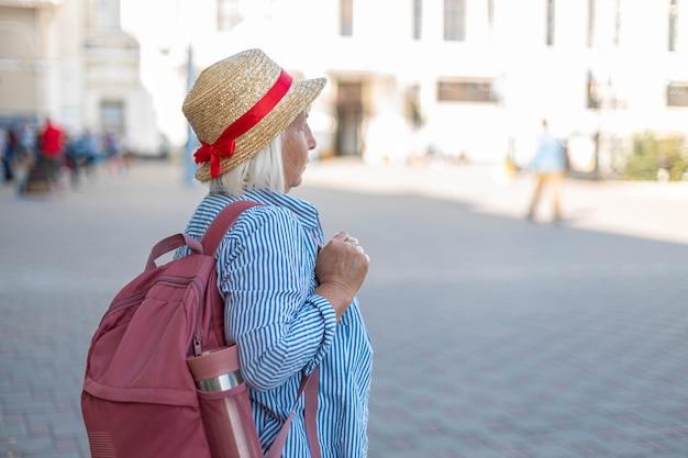 Touriste voyageur femme en vêtements décontractés bleus, chapeau avec sac à dos touristique en attente de vol.