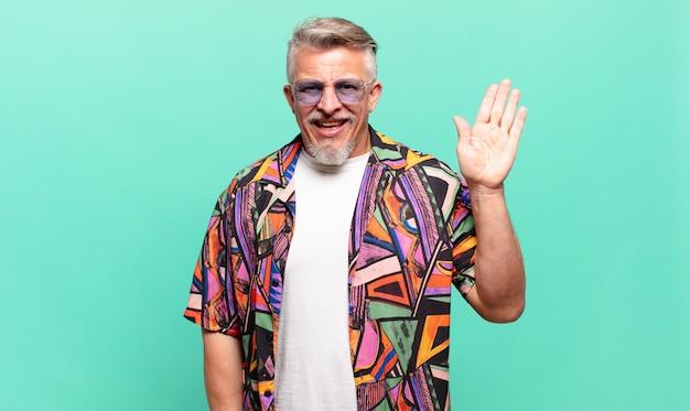 Touriste voyageur senior souriant joyeusement et gaiement, agitant la main, vous accueillant et vous saluant, ou vous disant au revoir