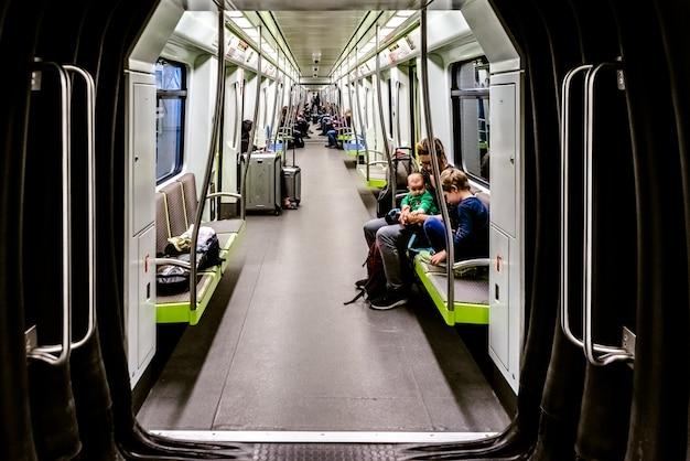 Les touristes à l'aéroport voyagent dans la voiture de métro.
