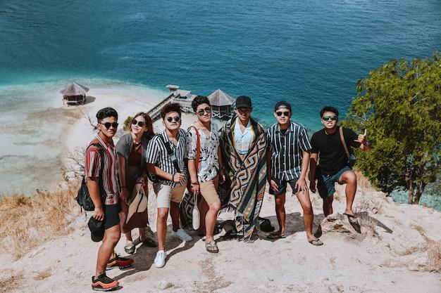 Les touristes asiatiques prennent une photo ensemble sur les collines avec la plage exotique de labuan bajo
