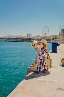 Les touristes à la côte avec des jumelles