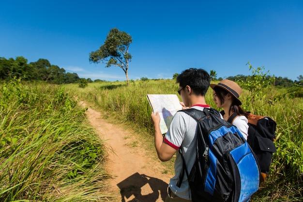 Touristes de couple ouvrant la carte touristique