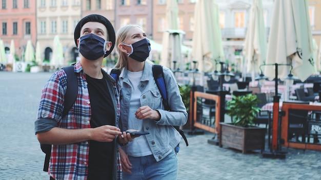 Les touristes dans des masques de protection et avec des sacs à l'aide de smartphone. ils recherchent des attractions touristiques intéressantes.