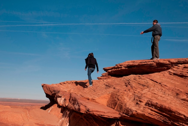 Touristes, debout, sur, a, rocher, horseshoe bend, glen canyon, secteur récréationnel national, arizona-utah, usa