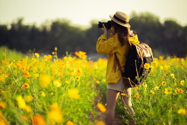 Touristes, elle prend des photos avec l'appareil photo dans le champ de fleurs