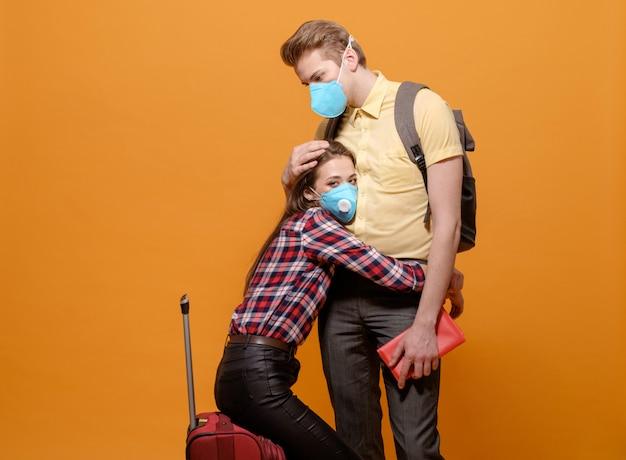 Touristes fatigués, voyageurs homme et femme dans des masques médicaux sur fond jaune orange, pandémie de coronavirus, pays frontaliers fermés, grande valise