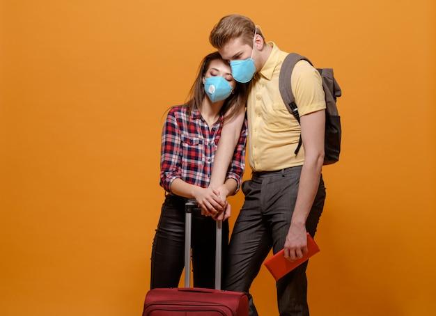 Touristes fatigués, voyageurs homme et femme dans des masques médicaux sur une orange jaune, pandémie de coronavirus, pays frontaliers fermés, grande valise