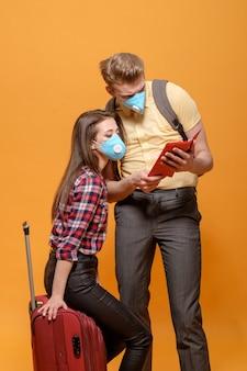 Les touristes fatigués les voyageurs homme et femme dans des masques médicaux pandémie de coronavirus fermé les pays frontaliers grande valise