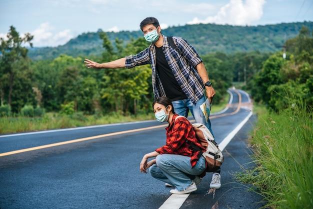 Les touristes féminines s'assoient, les touristes masculins font semblant d'auto-stoppeur portant un masque et sur le bord de la route.