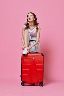Touristes de femme dans la robe blanche avec le fond rose de passager de mode de vie de valise rouge