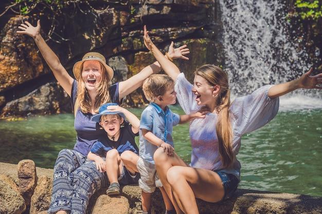 Touristes, femmes et enfants contre la cascade, les mains levées