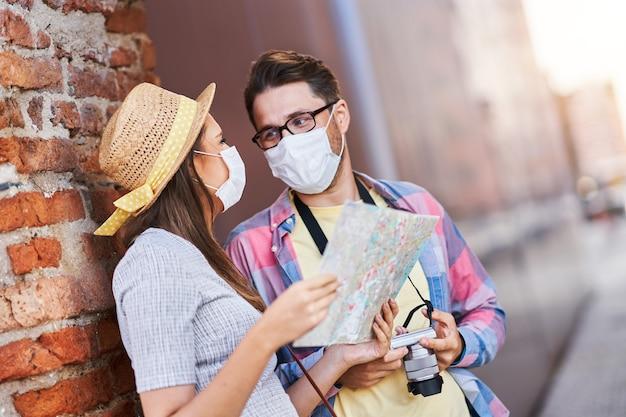 Touristes heureux adultes dans des masques visitant gdansk pologne en été