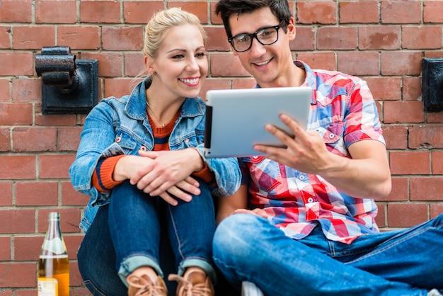 Touristes hipster planifiant des vacances à berlin avec ordinateur pad