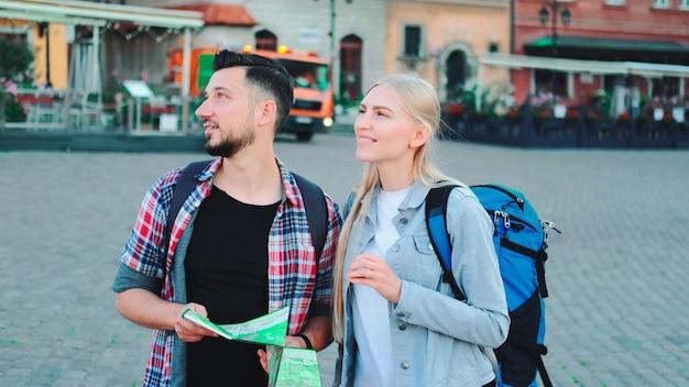 Touristes d'homme et de femme avec la carte recherchant le nouveau lieu historique au centre de la ville